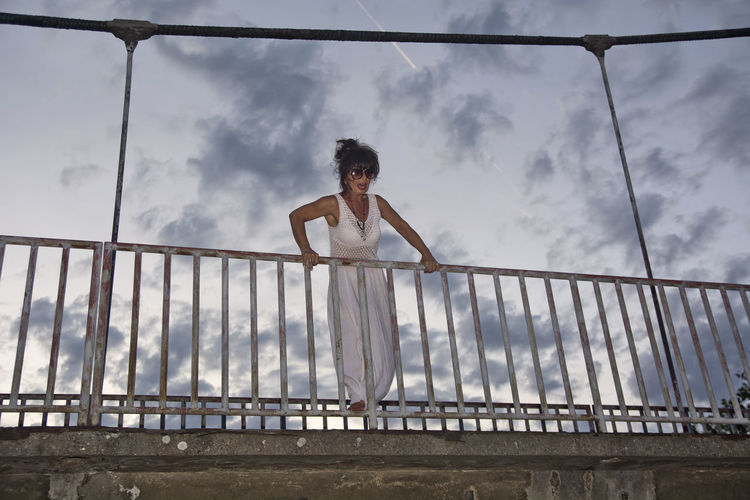Low angle view of senior woman standing by railing against sky