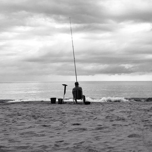 Man fishing in sea against sky