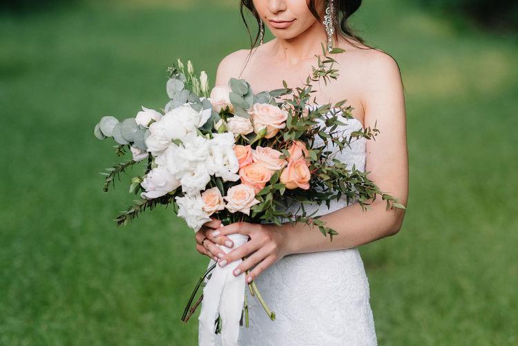 Beautiful woman standing by flower on field
