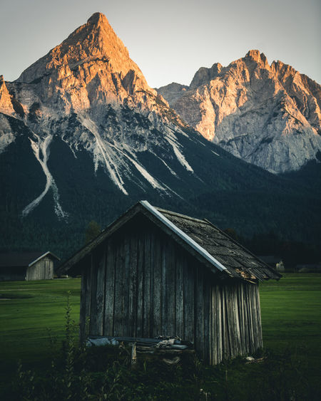 Log cabin on field against mountains