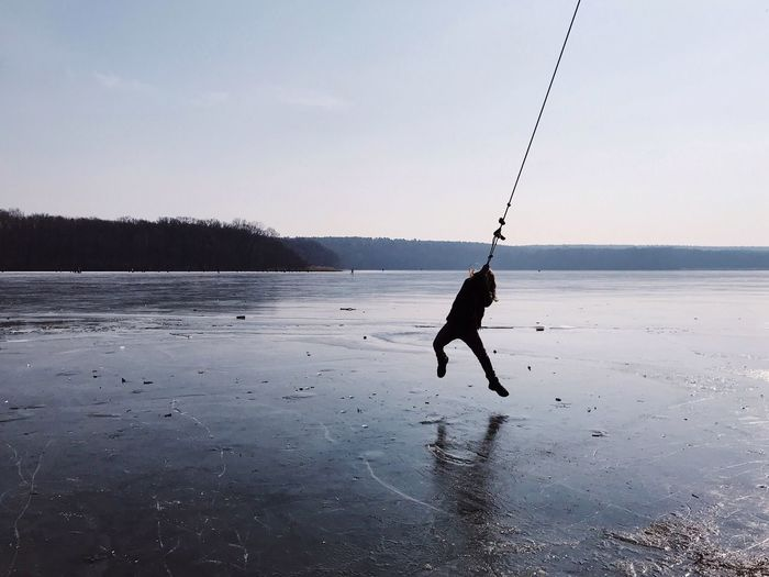 Silhouette of a boy swinging out over the ice on a frozen lake during winter