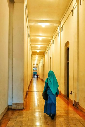 Rear view of woman walking in corridor of building