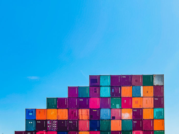 Stack of multi colored pier against blue sky