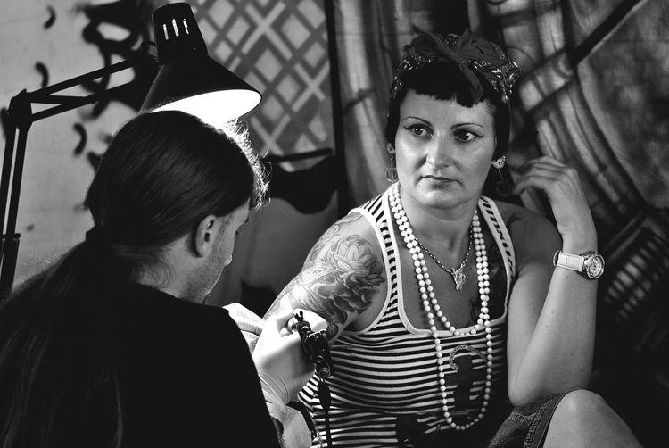 Artist making tattoo on woman hand