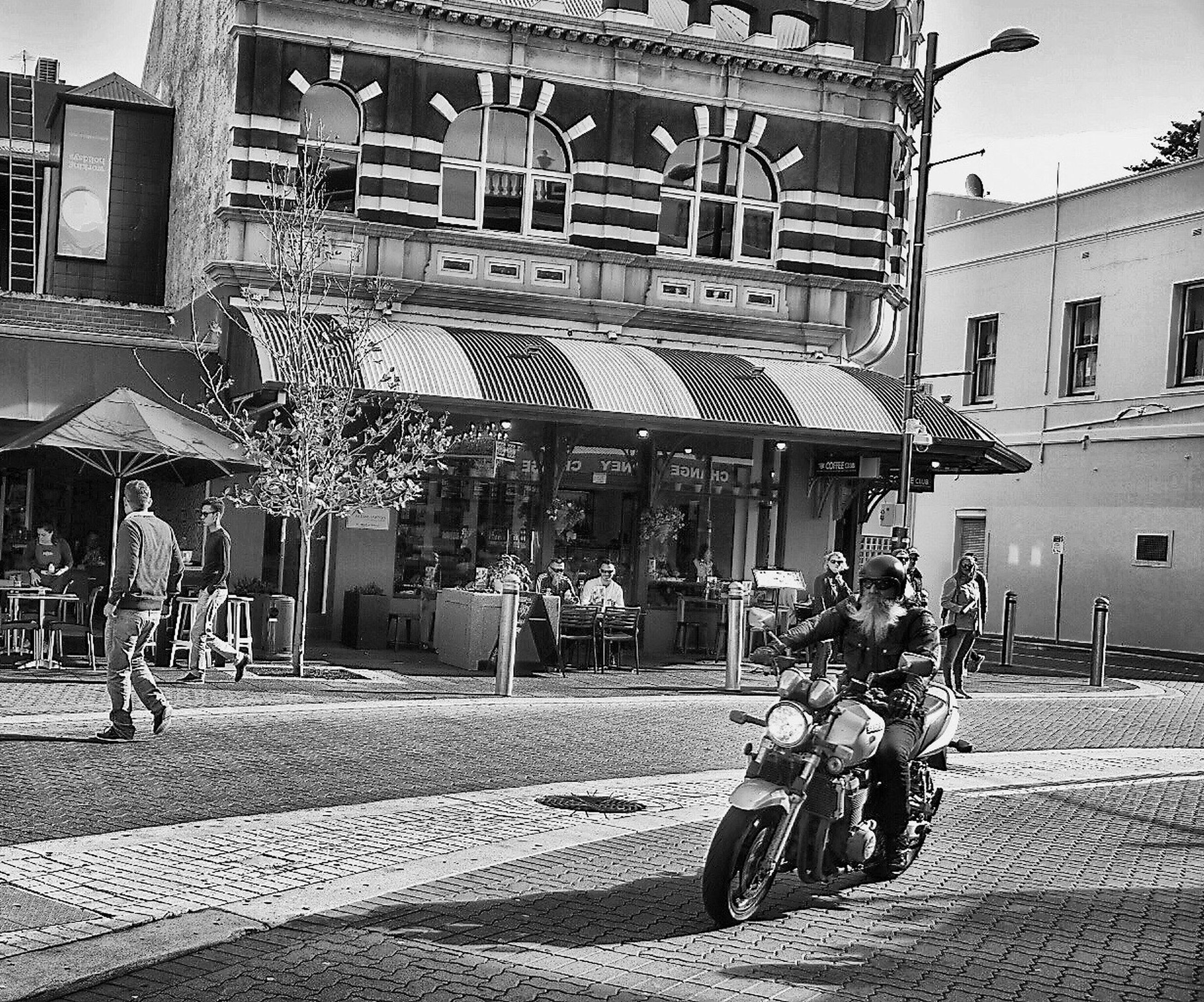 building exterior, built structure, architecture, transportation, street, outdoors, riding, two people, city, real people, day, women, motorcycle, men, lifestyles, full length, togetherness, adult, awning, people, mammal, sky, adults only