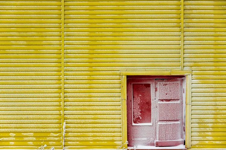 Snow covered red door in a yellow metal wall. Picture taken above the Arctic Circle in winter. Red Door Winter Architecture Arctic Backgrounds Building Exterior Cold Temperature Corrugated Day Door Entrance Full Frame House Metal Wall No People Pattern Polar  Snow Wall - Building Feature Yellow