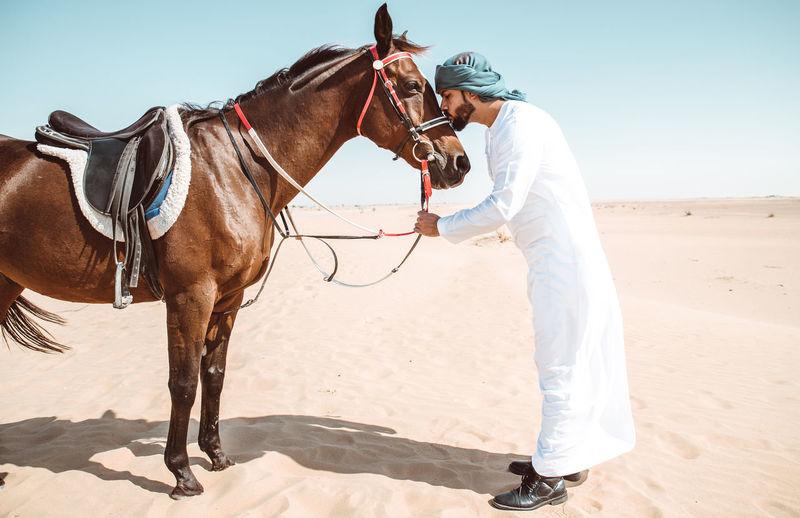 Full length of man kissing horse in desert against sky