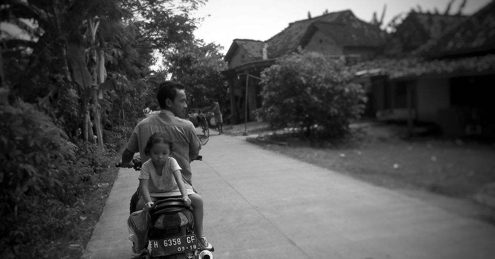 Man riding scooter with girl on road