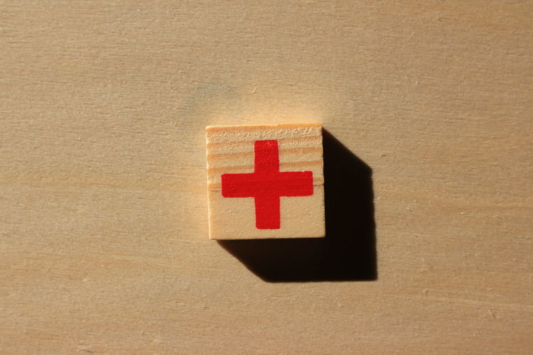 Close-up of plus sign on wood