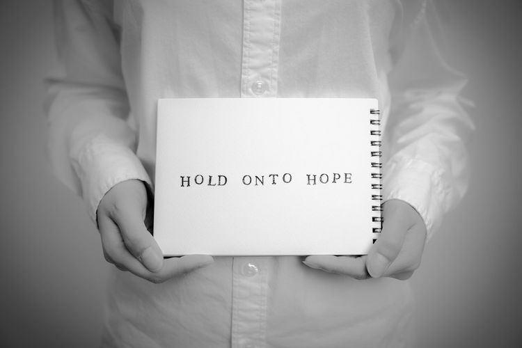 Midsection of person holding text on notepad against white background