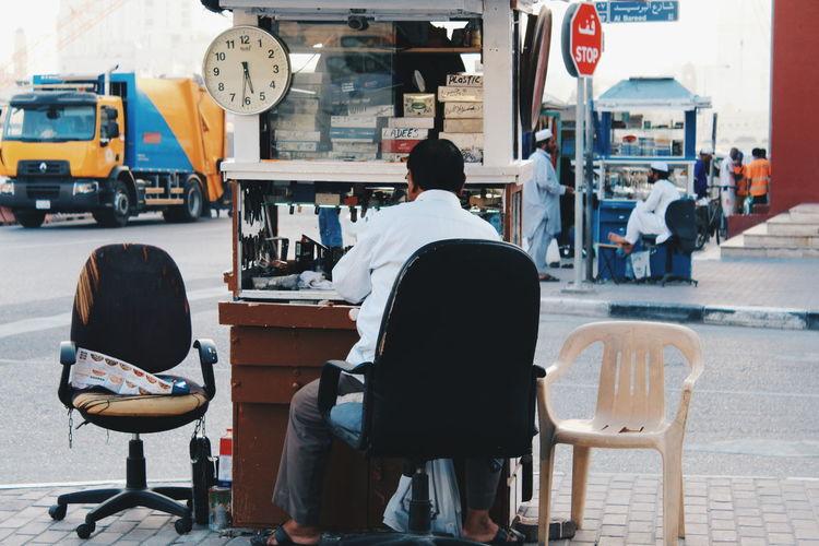 Rear view of clock repair street vendor sitting on chair