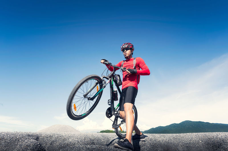 Full length of man riding bicycle on mountain