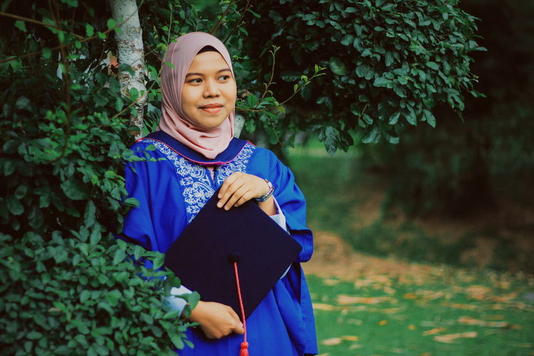 Smiling Young Woman Wearing Graduation Gown In Forest
