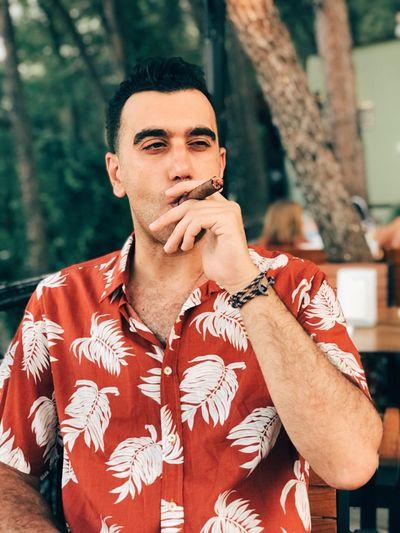 Man smoking cigar while sitting outdoors