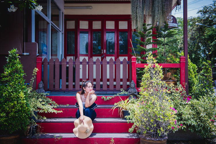 Woman sitting in yard against building
