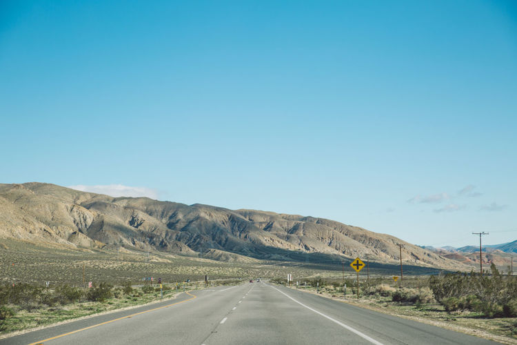 Arid Climate Asphalt Beauty In Nature Blue Clear Sky Day Desert Dividing Line Empty Landscape Mountain Mountain Range Nature No People Outdoors Road Road Marking Scenics Sky The Way Forward Tranquil Scene Tranquility Transportation White Line Winding Road