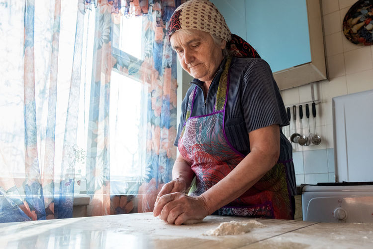 Grandmother cooking in the kitchen, kneading dough for bakery Real People Women Senior Adult Senior Women Kitchen Home Adult Domestic Room Domestic Life Casual Clothing Domestic Kitchen Home Interior Preparation  Preparing Food Indoors  Bakery Kneading Dough Making Wrinkled Skill  Granmother Cooking Preparation  Pasta