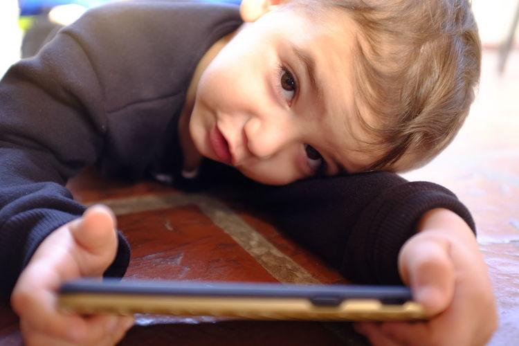 Portrait of cute boy using mobile phone