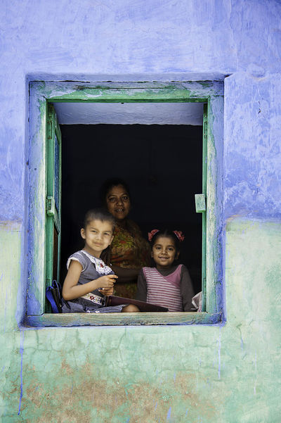 The three ladies of Jodhpur - These two little girls are doing their homework sitting on the window sill of their colorful house in Jodhpur, Rajasthan, India. Their mom is just behind them, partially hidden in the cooler shadow inside. When I show them my camera they nod permission to have their picture taken and a second later two of them smile and the third makes a face, like children do all around the world. Daughters Family India Jodhpur Mother Travel Photography Bonding Cheerful Childhood Colorful Family Values Friendly Girls Happiness Homework House Rajasthan Real People Smile Smiling Togetherness Travel Destinations Travelphotography Window Windowsill