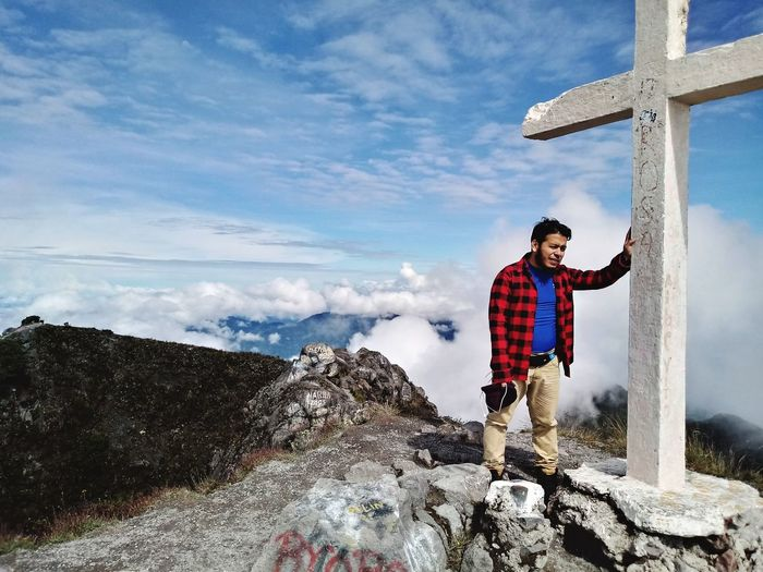 Man standing by cross on mountain against blue sky