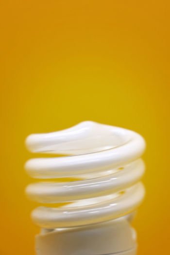 Spiral electric lamp bulb over yellow background, close up, side view Paint The Town Yellow Copy Space Light Bulb Close-up Colored Background Electricity  Freshness Idea Lamp Lamp Bulbs Lightning Equipment Source Of Light Spiral Bulb Spiral Lamp Template Yellow Yellow Background