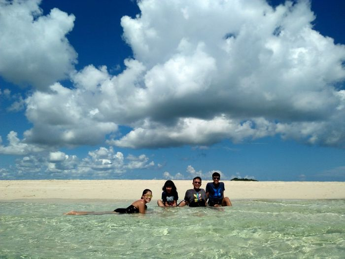 People sitting on beach against sky