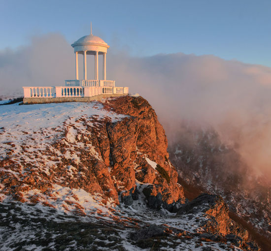 Gazebo on cliff against cloudy sky during winter