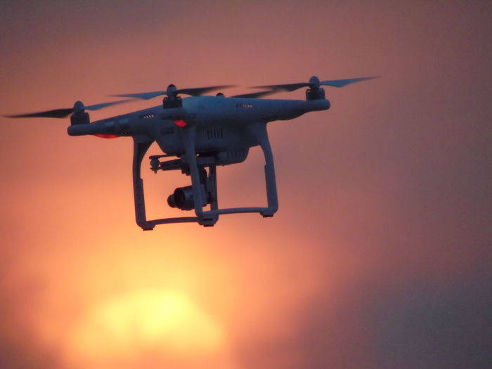 Low angle view of drone with camera flying against orange sky