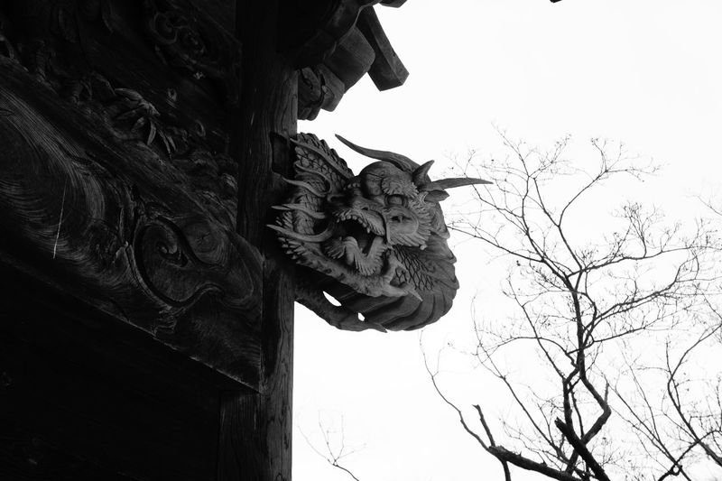 Dragon sculpture on traditional building against clear sky