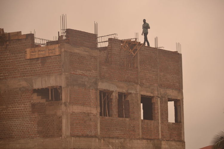 No Fear Of Heights Construction Worker Walking At High Altitude Built Structure Constructionsite Men At Work  Travel Photography Seen In Gulu, Uganda Cityscape