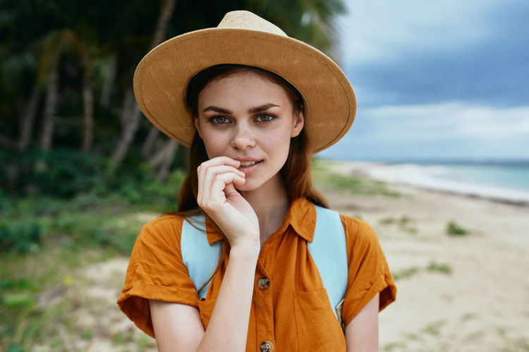 Portrait of young woman wearing hat standing on beach