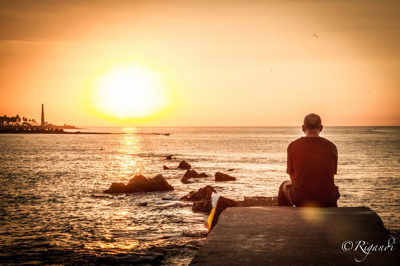 sunset, sea, water, beauty in nature, sun, real people, horizon over water, rear view, sunlight, scenics, one person, beach, nature, sky, sitting, leisure activity, tranquility, men, lifestyles, clear sky, outdoors, vacations, nautical vessel, wave, day, people
