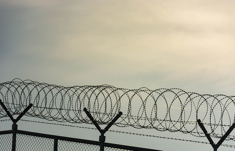 Barbed Wire Fence Used For Protection Purposes Of Property And Imprisonment, No Freedom, Barbed Wire On fence With Blue Sky To Feel Worrying. Crime Freedom Barbed Fence Barbed Wire Fence Imprison Outdoors Prison Protection Razor Wire Safety Security Sky Wire Worry