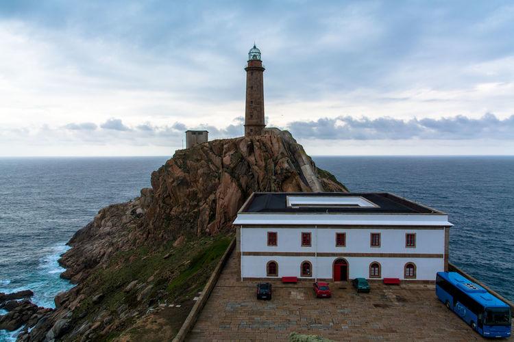 Lighthouse in sea against sky