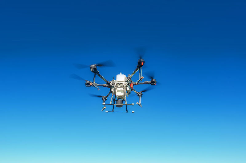 Agricultural drone in flight on a background of blue sky. field spraying new technologies.