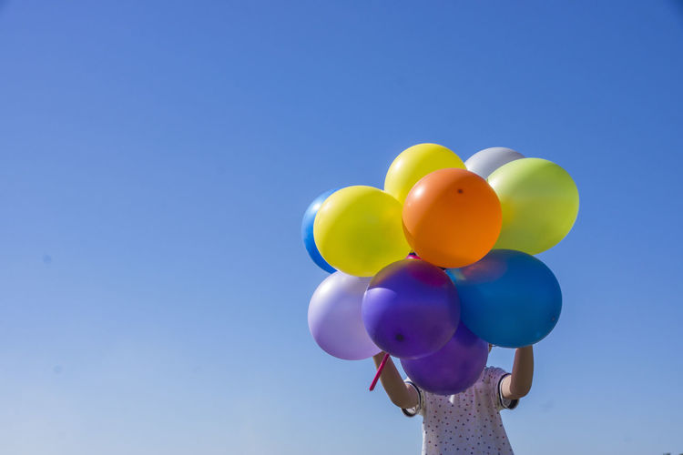 Low angle view of boy holding multi colored balloons against clear blue sky