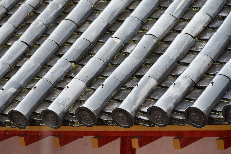 High angle view of wet ceramic tiles on japanese temple roof