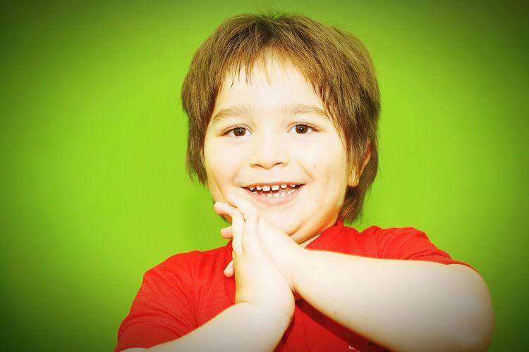 Portrait of smiling boy against green background