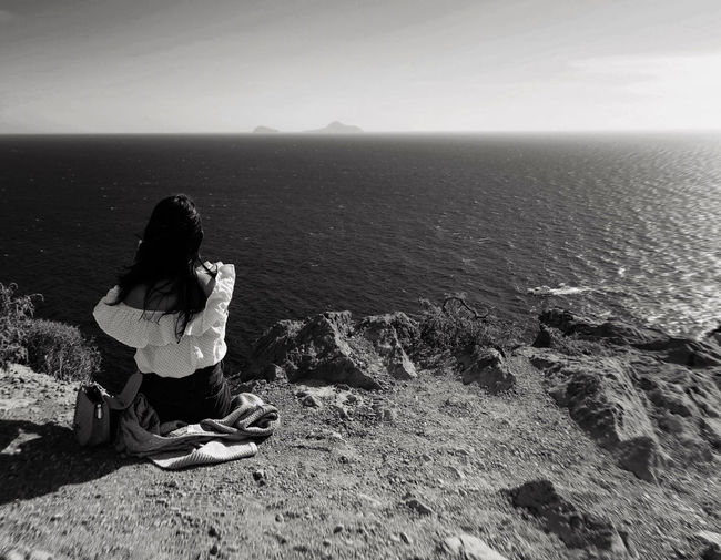 Woman sitting on rock looking at sea
