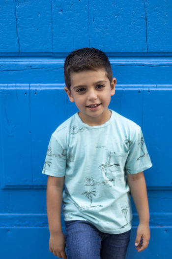 Portrait of boy standing against blue door