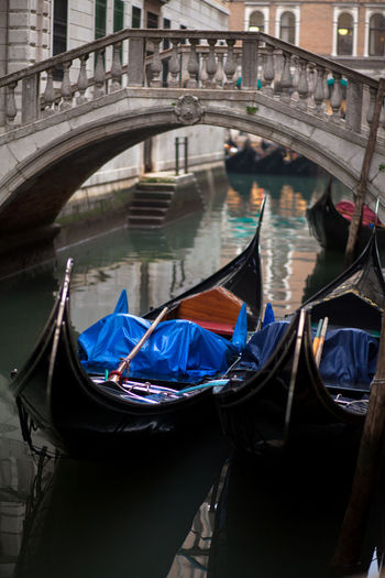 Boats in canal against footbridge