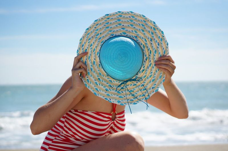 Midsection of woman wearing hat on beach against sky