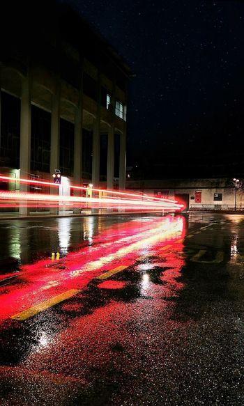 Light trails on wet street at night
