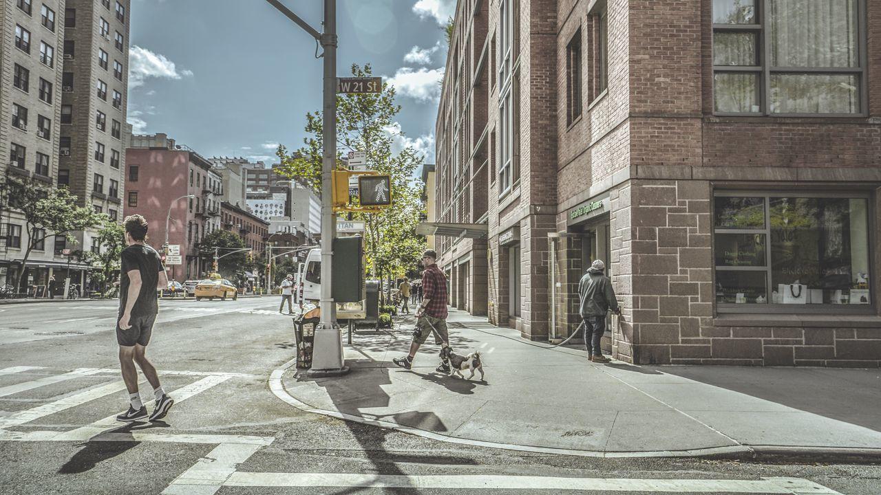 MAN ON STREET AGAINST BUILDINGS