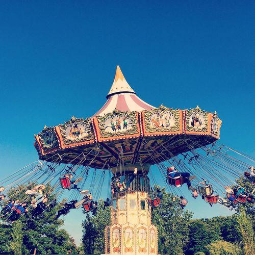 Amusement park against clear blue sky