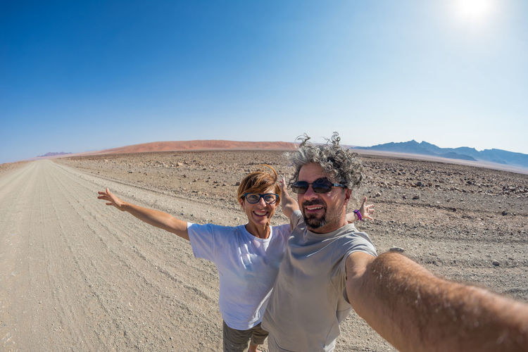 Portrait of smiling mature couple standing on desert road