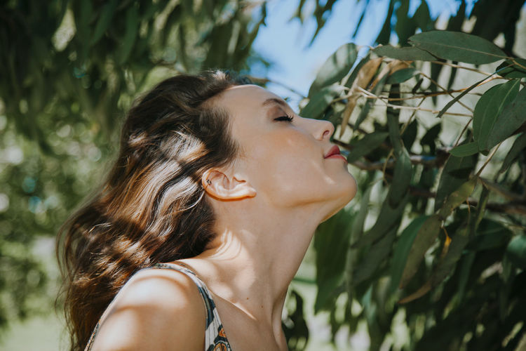 Side view of woman smelling by tree