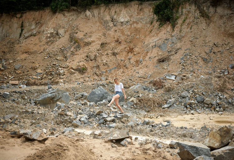 Full length of woman walking on rocks