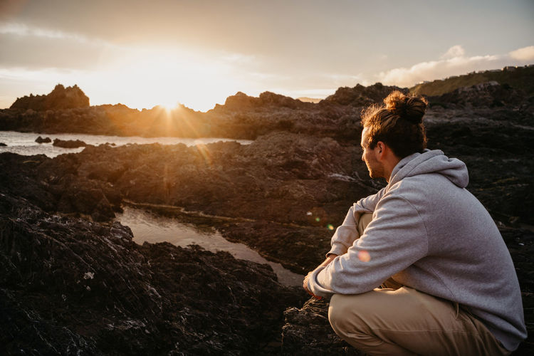 Side View Of Man Crouching On Rock Against Sky During Sunset