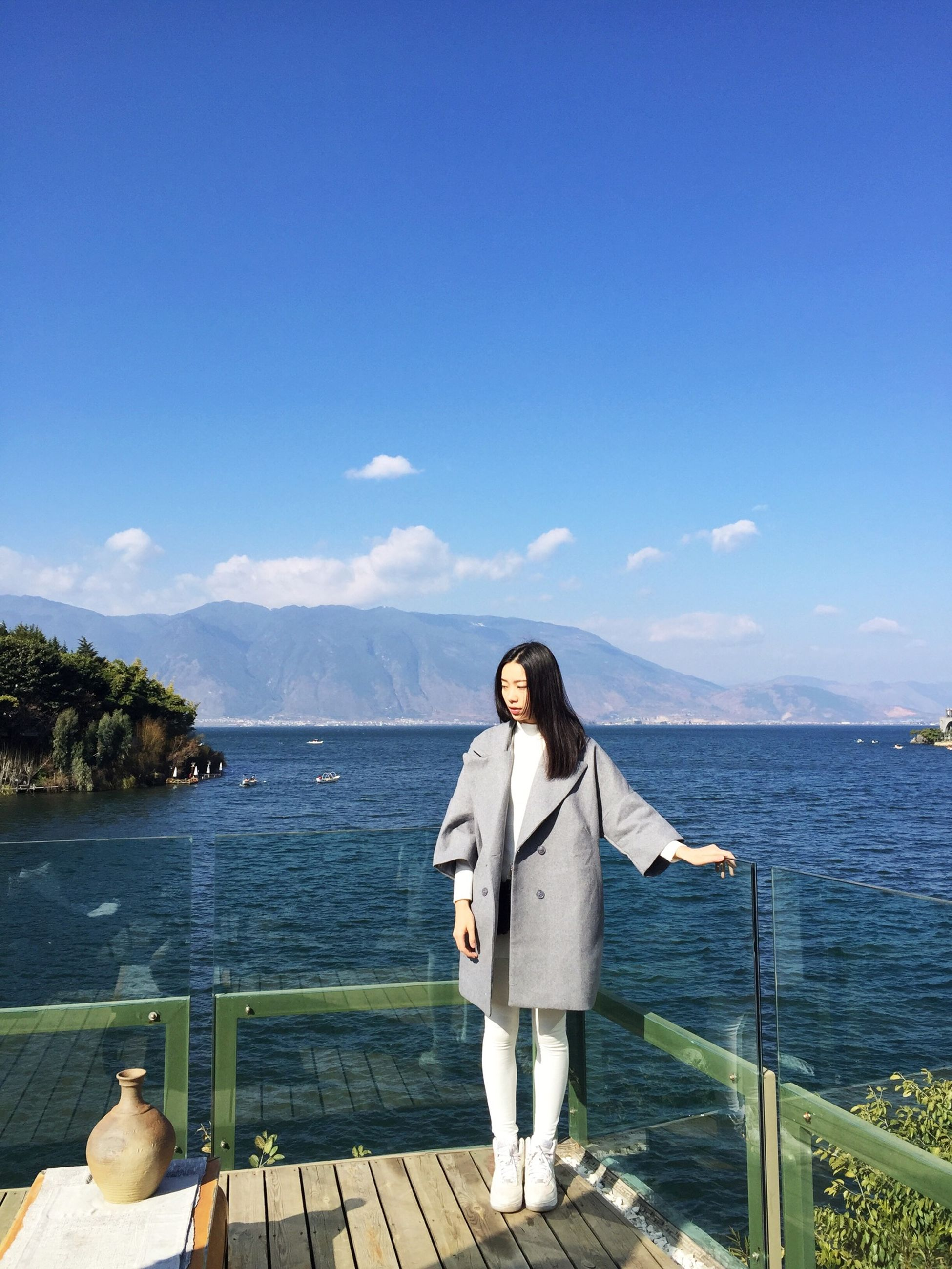 water, sea, sky, rear view, blue, lifestyles, leisure activity, railing, scenics, nature, standing, tranquility, beauty in nature, casual clothing, tranquil scene, full length, mountain, sitting